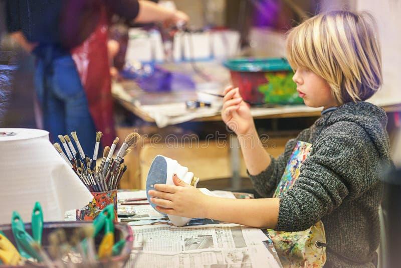 VENEZA, ITÁLIA - 02 23 2019: Cara feliz das mãos do rapaz pequeno com máscara do carnaval da tradição de Veneza, pintura, fazendo foto de stock
