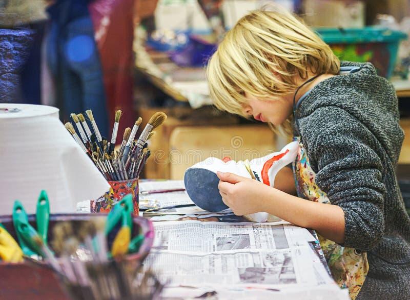 VENEZA, ITÁLIA - 02 23 2019: Cara feliz das mãos do rapaz pequeno com máscara do carnaval da tradição de Veneza, pintura, fazendo fotos de stock