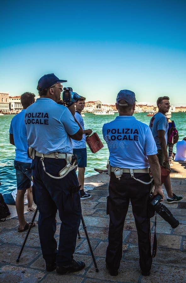 VENEZA, ITÁLIA - 17 DE AGOSTO DE 2016: Turistas do relógio dos agentes da polícia através do equipamento ótico especial o 17 de a foto de stock