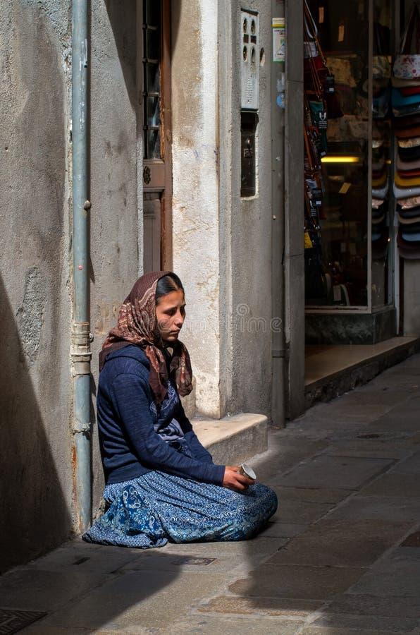 Veneza, Itália - 7 de maio de 2018: Um mendigo fêmea desabrigado está implorando na rua em Veneza, Itália Uma mulher do mendigo g imagem de stock