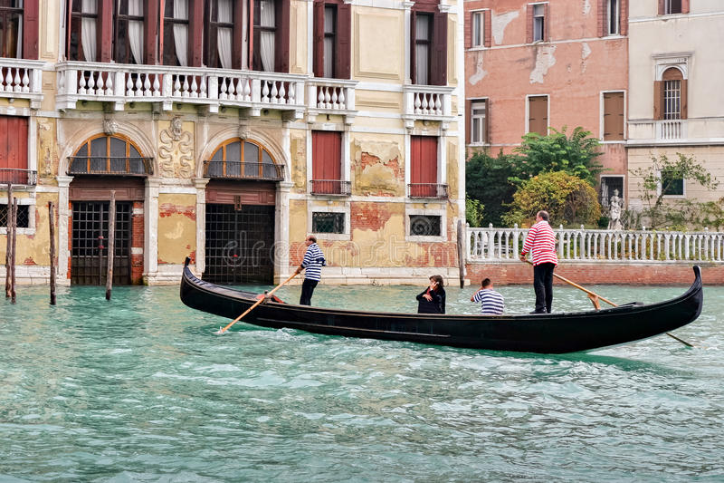 VENEZA, ITÁLIA - 26 DE OUTUBRO: Dois gondoleiros que ferrying passageiros imagem de stock royalty free