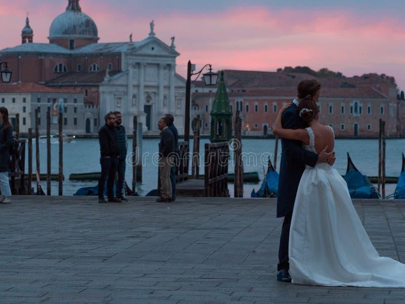 VENEZA, ITÁLIA - 8 DE OUTUBRO DE 2017: noivos que abraçam na praça San Marco, gôndola no fundo imagens de stock