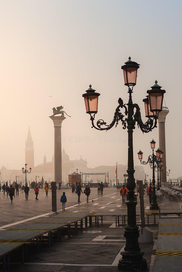 VENEZA, ITÁLIA - 6 DE OUTUBRO DE 2017: Tourits no quadrado de San Marco no nascer do sol fotografia de stock royalty free