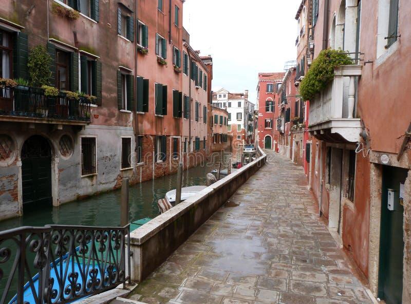 Veneza - uma vista de um canal pequeno com barcos e a rua fotografia de stock