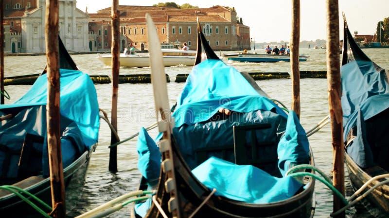 VENEZIA, ITALIA - 8 AGOSTO 2017 Gondole veneziane attraccate che ondeggiano contro il paesaggio urbano ed i motoscafi commoventi fotografia stock