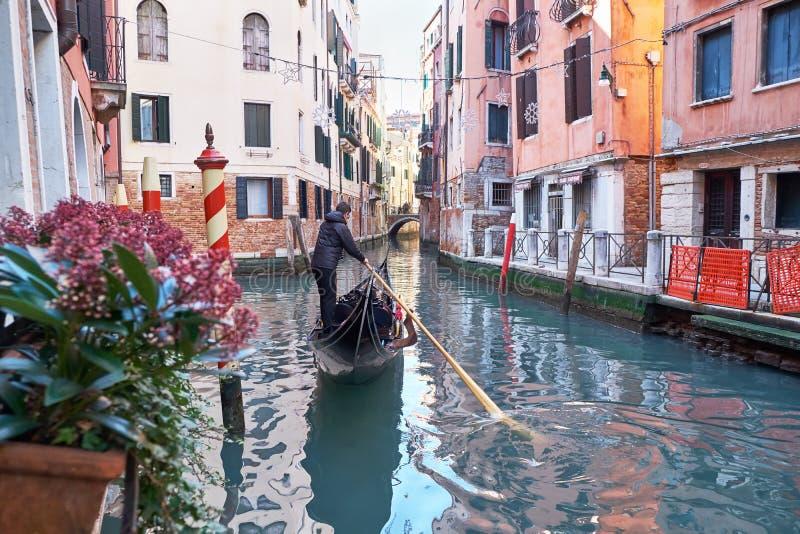 Venezia, Italia - 10 febbraio 2018: Le gondoliere guidano la gondola tramite il canale stretto fra le case storiche variopinte immagine stock libera da diritti