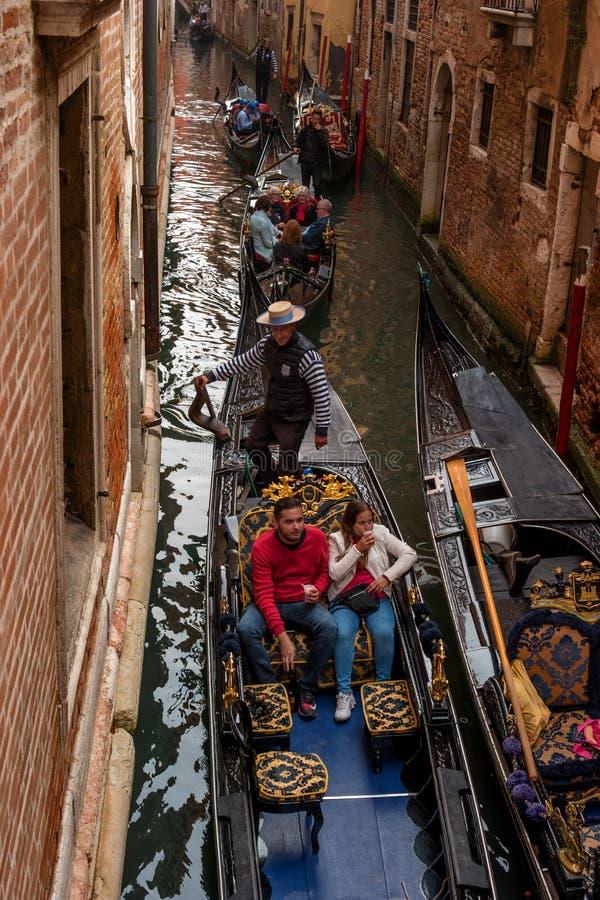 Venezia, Italia - 13 ottobre 2017: I turisti navigano su una gondola su un canale stretto La gondola pienamente è decorata con ro fotografia stock
