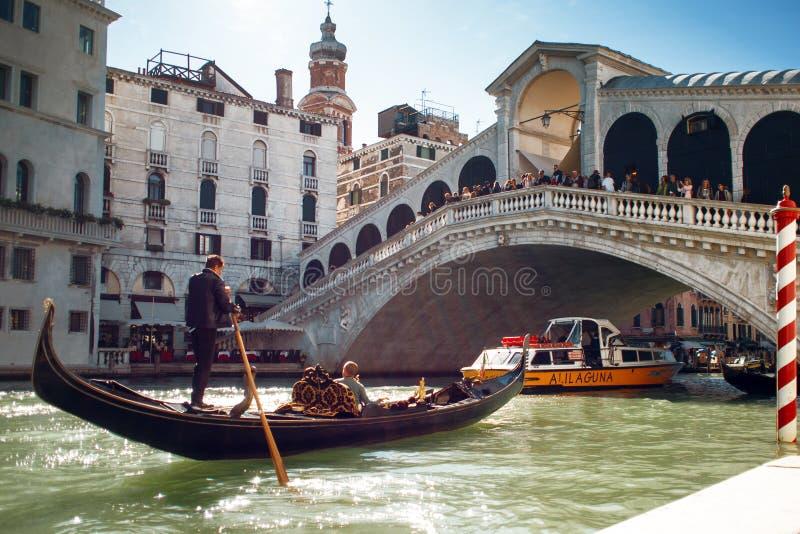 VENEZIA, ITALIA - 7 OTTOBRE 2017: Le gondoliere galleggiano su Grand Canal, il ponte di Rialto nei precedenti fotografia stock