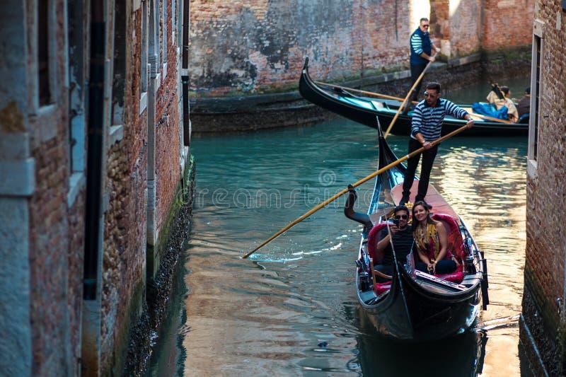 VENEZIA, ITALIA - 7 OTTOBRE 2017: Le gondoliere galleggiano sul canale stretto a Venezia, Italia fotografia stock libera da diritti