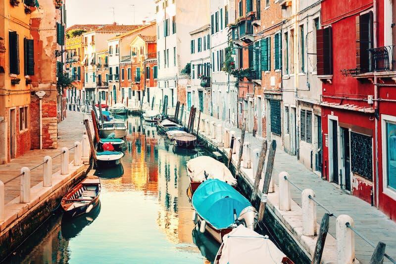 Venezia, Italia Piccolo canale con le barche ed i vecchi monumenti storici fotografia stock
