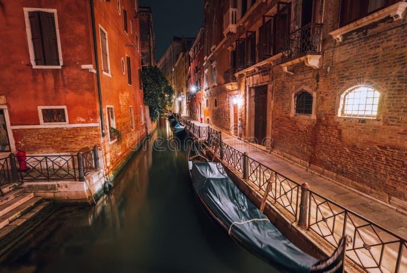 Venezia Italy. Narrow channel and gondola boats in lagoon city venice at night. Long exposure photo.  stock photography
