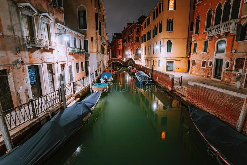 Venezia Italy. Narrow channel and gondola boats in lagoon city venice at night. Vivid colored old brick buildings around.  stock images