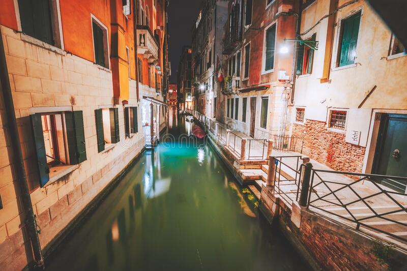 Venezia narrow channel and gondola boats in lagoon city Venice at night. Italy. Vivid colored old brick buildings street.  royalty free stock images