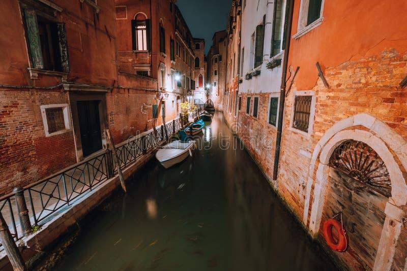 Venezia at night. Narrow channel and gondola boats in lagoon river city of venice. Long exposure photo.  stock photography