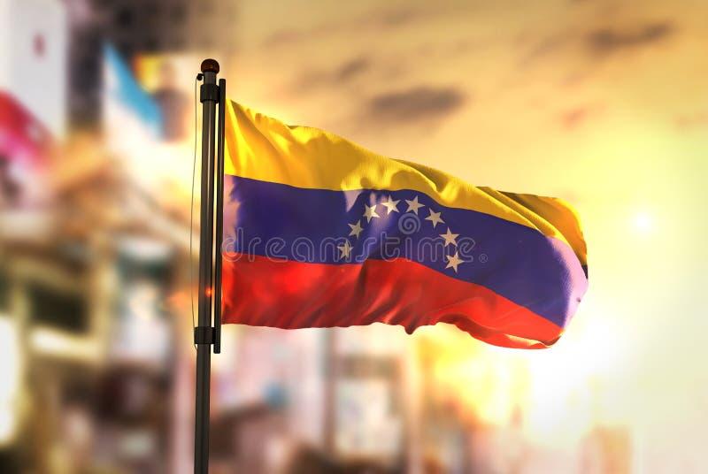 Venezuela Flag Against City Blurred Background At Sunrise Backlight. Sky royalty free stock photos