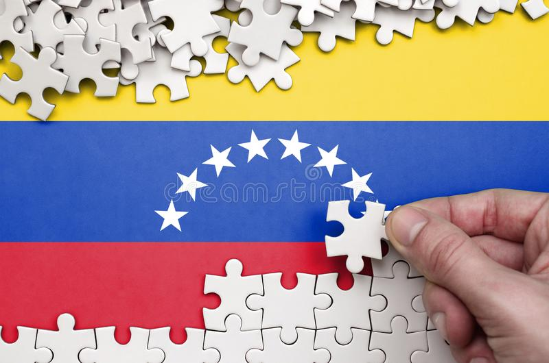 Venezuela flag is depicted on a table on which the human hand folds a puzzle of white color stock photos