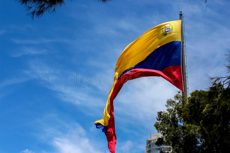 Venezuela flag waving in the wind, blue sky cleared. Yellow, blue and red colors stock images