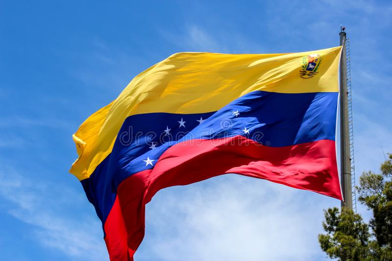 Venezuela flag waving in the wind, blue sky cleared. Yellow, blue and red colors royalty free stock image