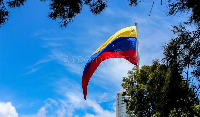 Venezuela flag waving in the wind, blue sky cleared. Yellow, blue and red colors royalty free stock photography