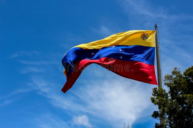 Venezuela flag waving in the wind, blue sky cleared. Yellow, blue and red colors stock image