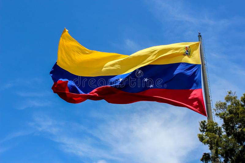Venezuela flag waving in the wind, blue sky cleared. Yellow, blue and red colors royalty free stock photos