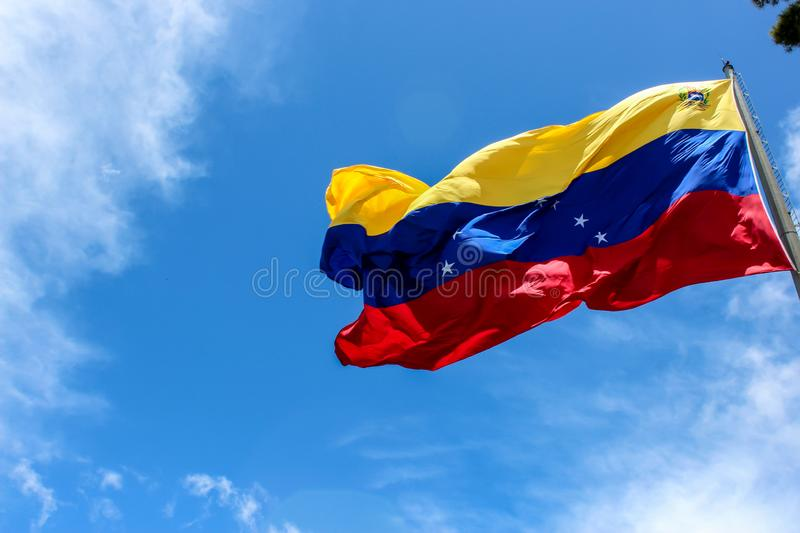 Venezuela flag waving in the wind, blue sky cleared. Yellow, blue and red colors royalty free stock photo