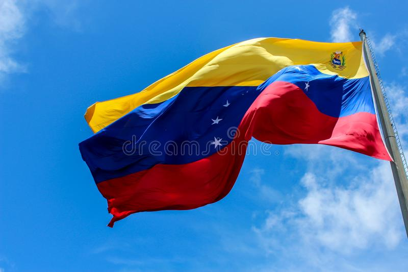 Venezuela flag waving in the wind, blue sky cleared. Yellow, blue and red colors royalty free stock images