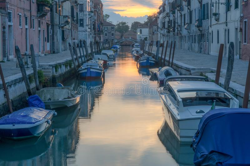 Venice canal with parked boats. During the sunset. Reflective water royalty free stock photos