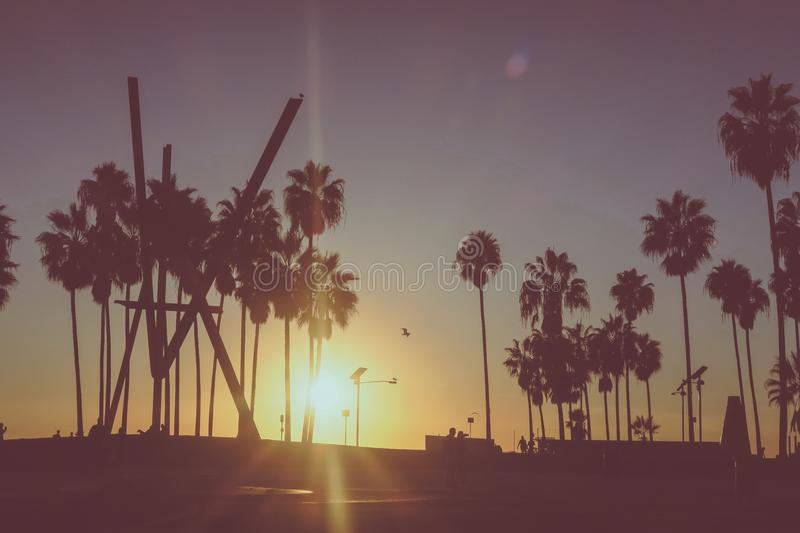 Venice beach Sunset in Los Angeles with a pedestrian walk during. Beautiful Venice beach area in Los Angeles with a pedestrian walk during orange sunset. Empty royalty free stock photo