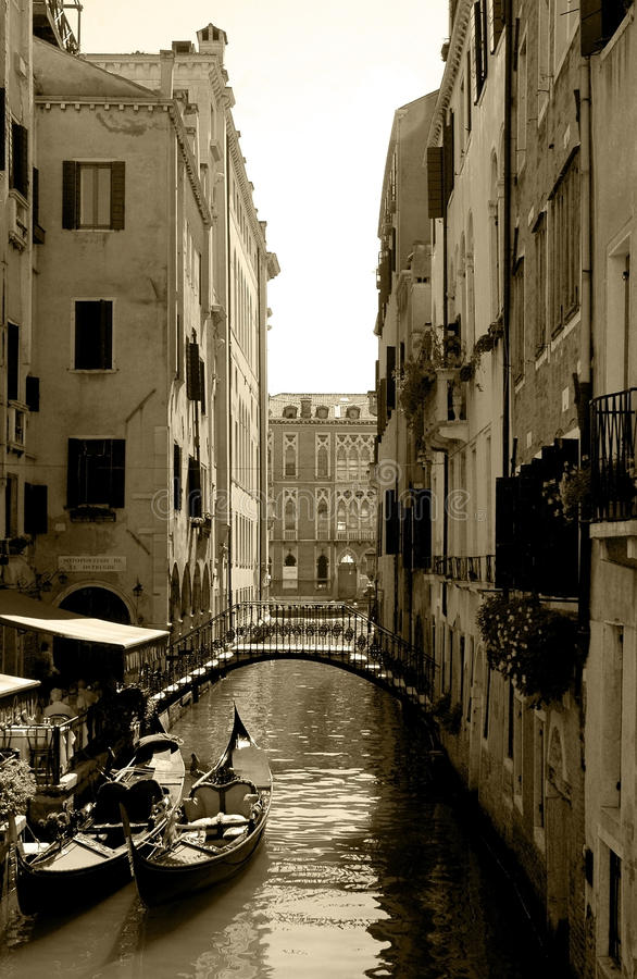 Venice Canal, Iron Bridge, Gondolas, Cafe Restaurant Terrace - Sepia. Gondolas parked near an iron bridge in a parallel alley canal to the Grand Canal of Venice stock images