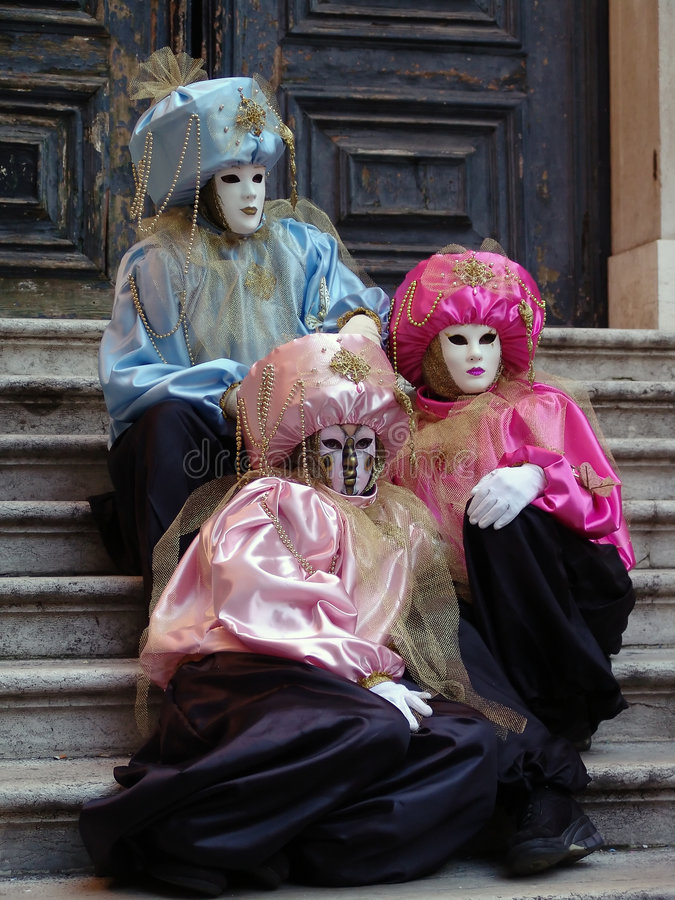 Venice carnival. Venice masks sitting on stairs stock images