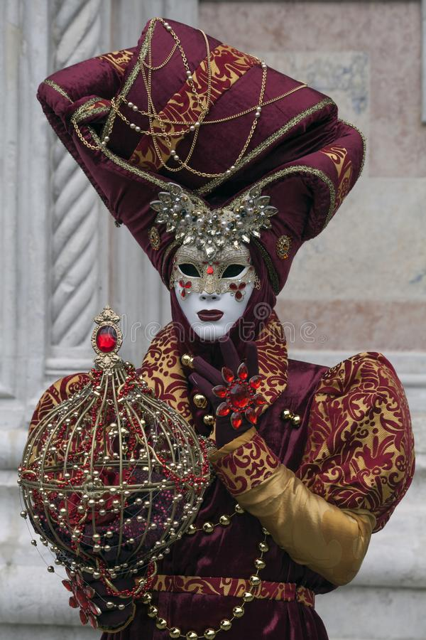 Venetian Carnival character dressed in a colourful red and gold costume and Venice mask in February Venice Italy. Venetian Carnival character dressed in a royalty free stock photos