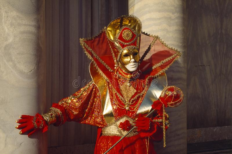Venice mask dressed in a red and gold costume at Venice Carnival in February, Venice Italy. Venice mask dressed in a red and gold costume at Venice Carnival royalty free stock images