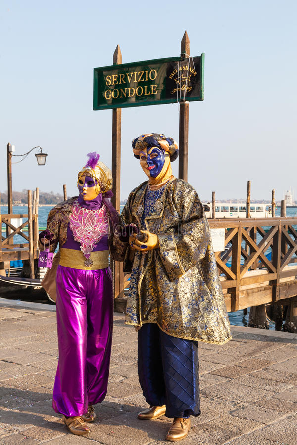 Venice 2017 Carnival, Italy. Colorful couple at the lagoon under. A gondola sign at Piazza San marco with jetties and a vaporetto passing behind them in a full stock photos