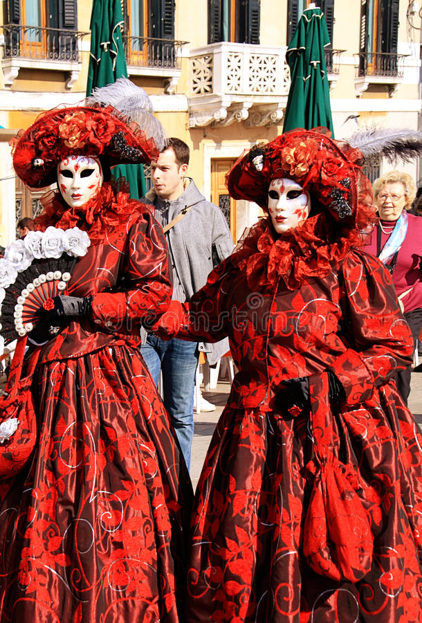 Venice Carnival, two women with red costumes and masks royalty free stock image