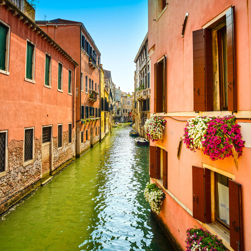 Venice cityscape, Cannaregio water canal, flowers and boats. Italy royalty free stock photo