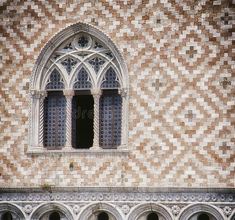 Venice, Doge` s palace, Palazzo Ducale, facade detail. Venice, palazzo Ducale: detail of tripled arcade window and facade decoration with alternate red marble stock photos