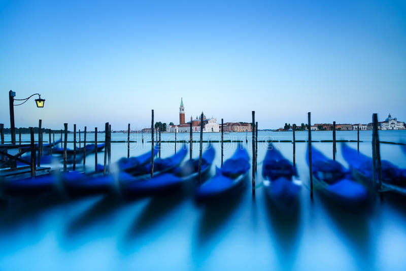 Venice, gondolas or gondole on sunset and church on background. Italy. Venice, gondolas or gondole on a blue sunset twilight and San Giorgio Maggiore church stock photos