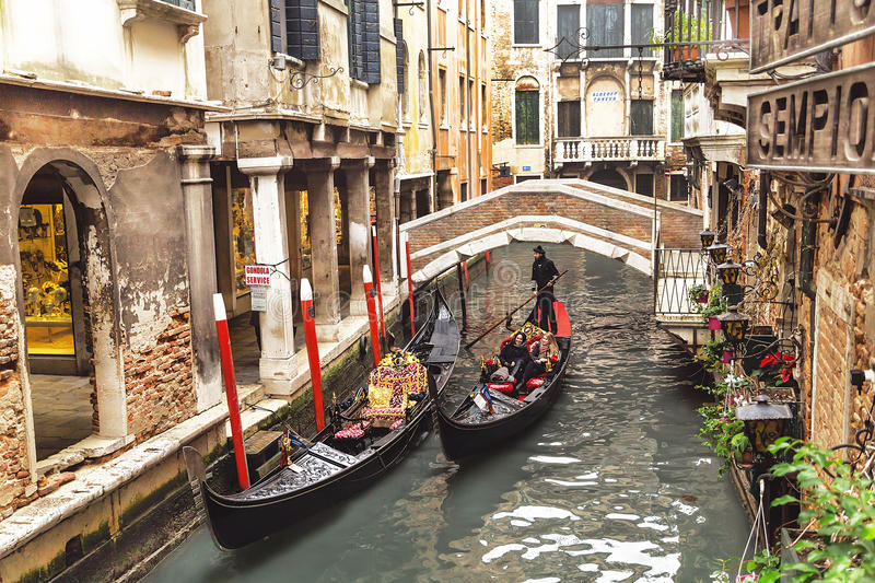 Venice, Italy – December 21, 2015: Venetian gondolier punting gondola with tourists through canal. Venice. Italy. royalty free stock photo