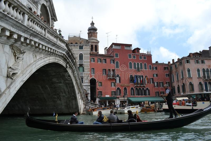 Gondola is passing along the Grand canal under the beautiful Rialto bridge in a sunny spring day. stock photos