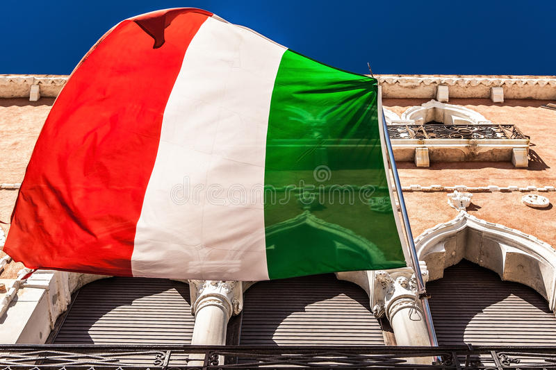 VENICE, ITALY - AUGUST 20, 2016: Italian flag and facades of old medieval buildings close-up on August 20, 2016 in Venice, Italy stock photos