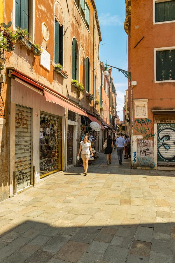 VENICE, ITALY - August 02, 2019: Narrow pedestrian streets of Venice. Locals and tourists strolling along the historical buildings royalty free stock photography