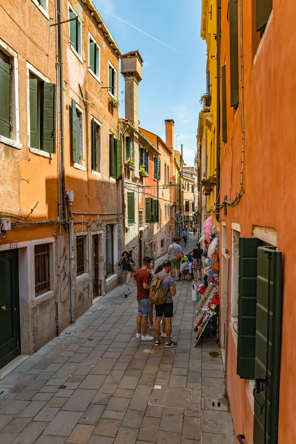 VENICE, ITALY - August 02, 2019: Narrow pedestrian streets of Venice. Locals and tourists strolling along the historical buildings stock photography