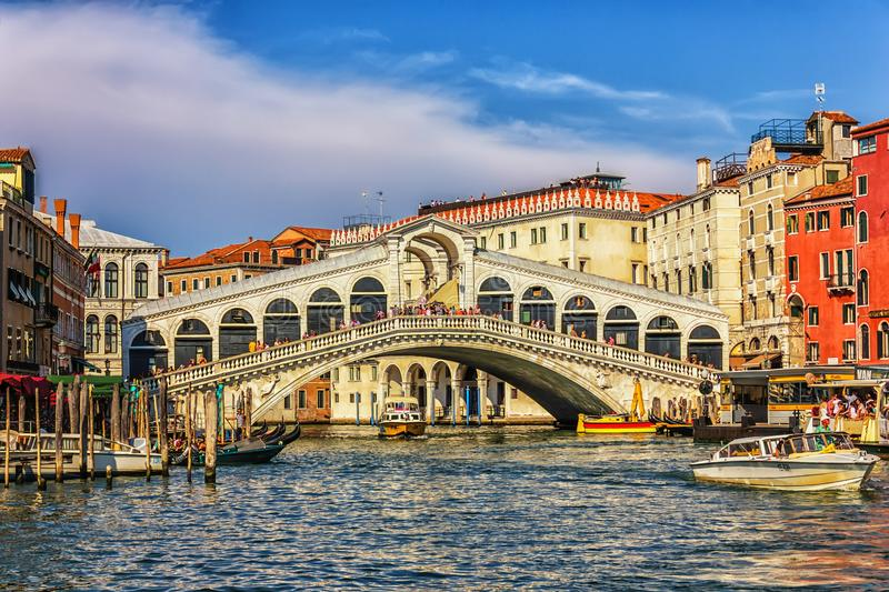 Venice, Italy - August 22, 2018: The Rialto bridge, a vaporetto, a ferry berth and gondolas in Grand Canal royalty free stock photography