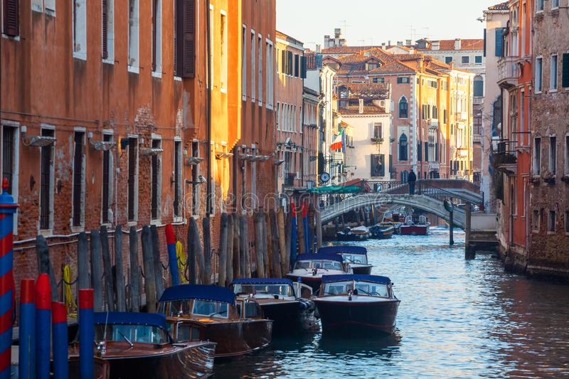 Venice, Italy - 14.03.2018: Boats on narrow canal between colorful historic houses in Venice royalty free stock images
