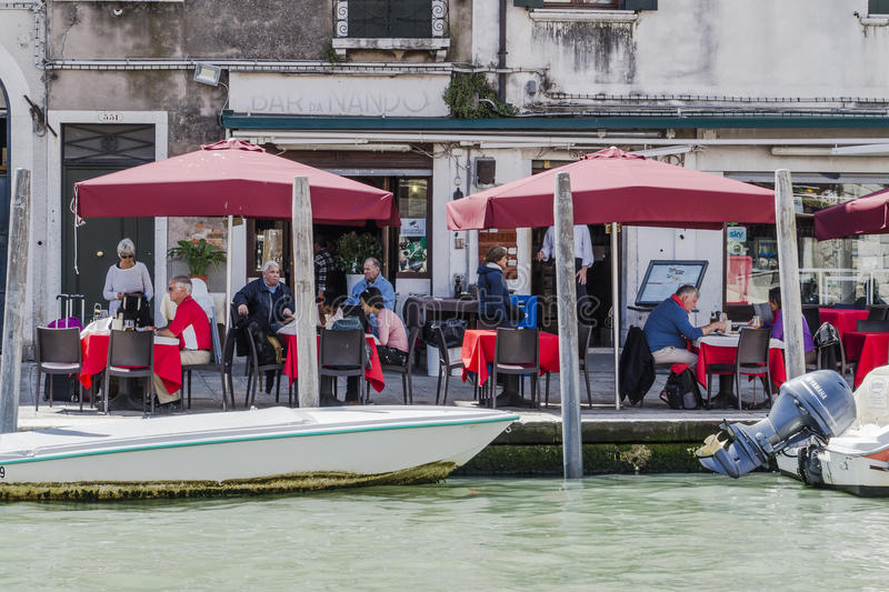 Venice in Italy. Canal with the boats in Venice , Italy , Europe. And people in the restaurants garden stock photos
