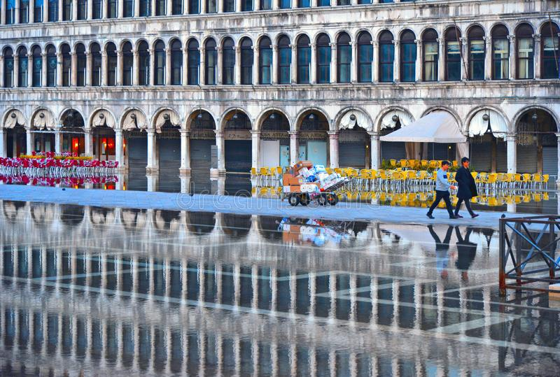 VENICE,ITALY Empty St Mark`s Square during a flood with beautiful water reflections of historical buildings on wet f royalty free stock images