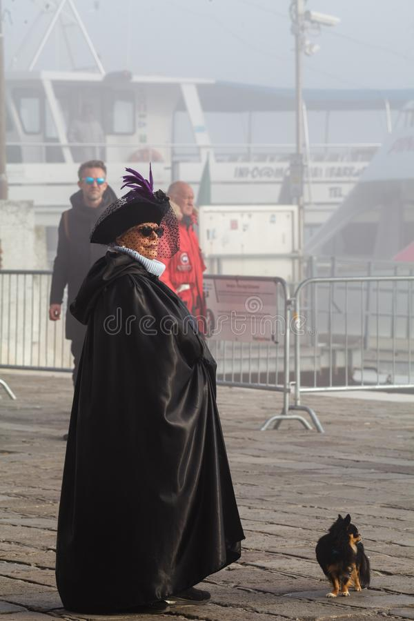 VENICE, ITALY – FEBRUARY 22, 2019: A lady with a dog in a carnival costume on the quay of San Marco royalty free stock photo