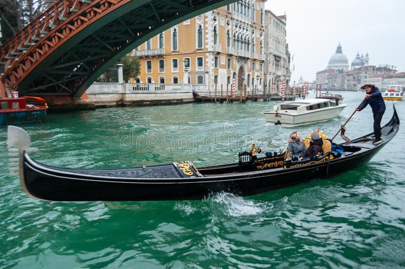 Venice, Italy - 09 February 2019: Ponte dell`Accademia and gondola passing under the bridge over grand canal stock image