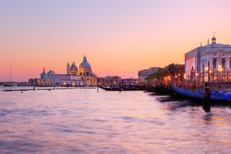 Venice, Italy. Gondolas on Grand Canal at sunset. Basilica Santa Maria della Salute in the background royalty free stock photography